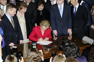 a group of smiling people stand around a woman signing a document.