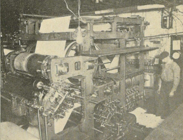 A black and white photograph of a large newspaper printer.