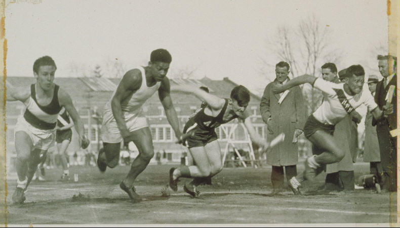 Four men at the start of a relay race, two of whom are minorities. Five men on the sidelines and two additional figures in the background. Willis Nichols Hawley Armory is also in the background.