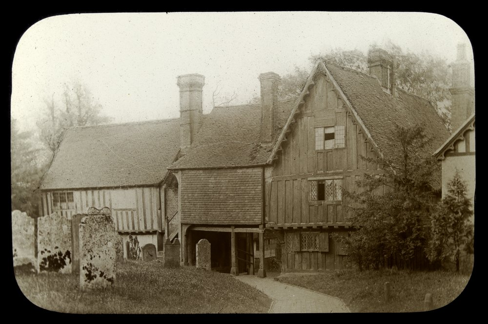 Wooden buildings with steep gabled roofs, grave stones on right [Historic buildings, England],