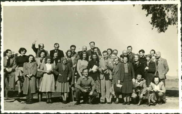 Group of men and women, with man holding dog in foreground, Bonegilla