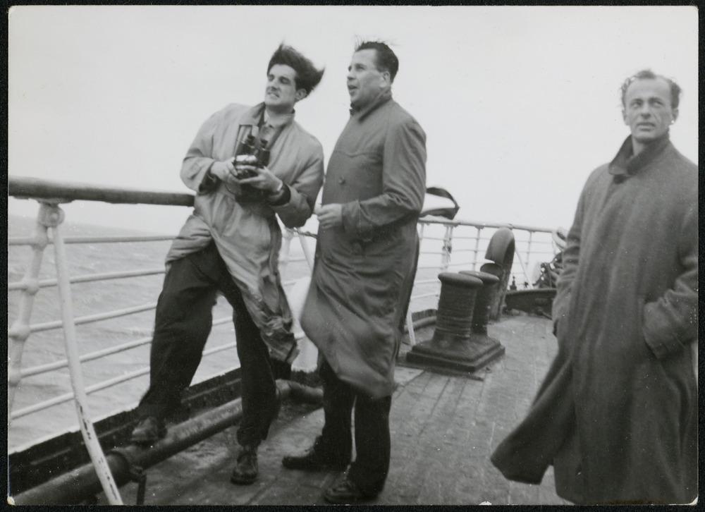Three men standing on deck of the ship Liguria, enroute to Australia.