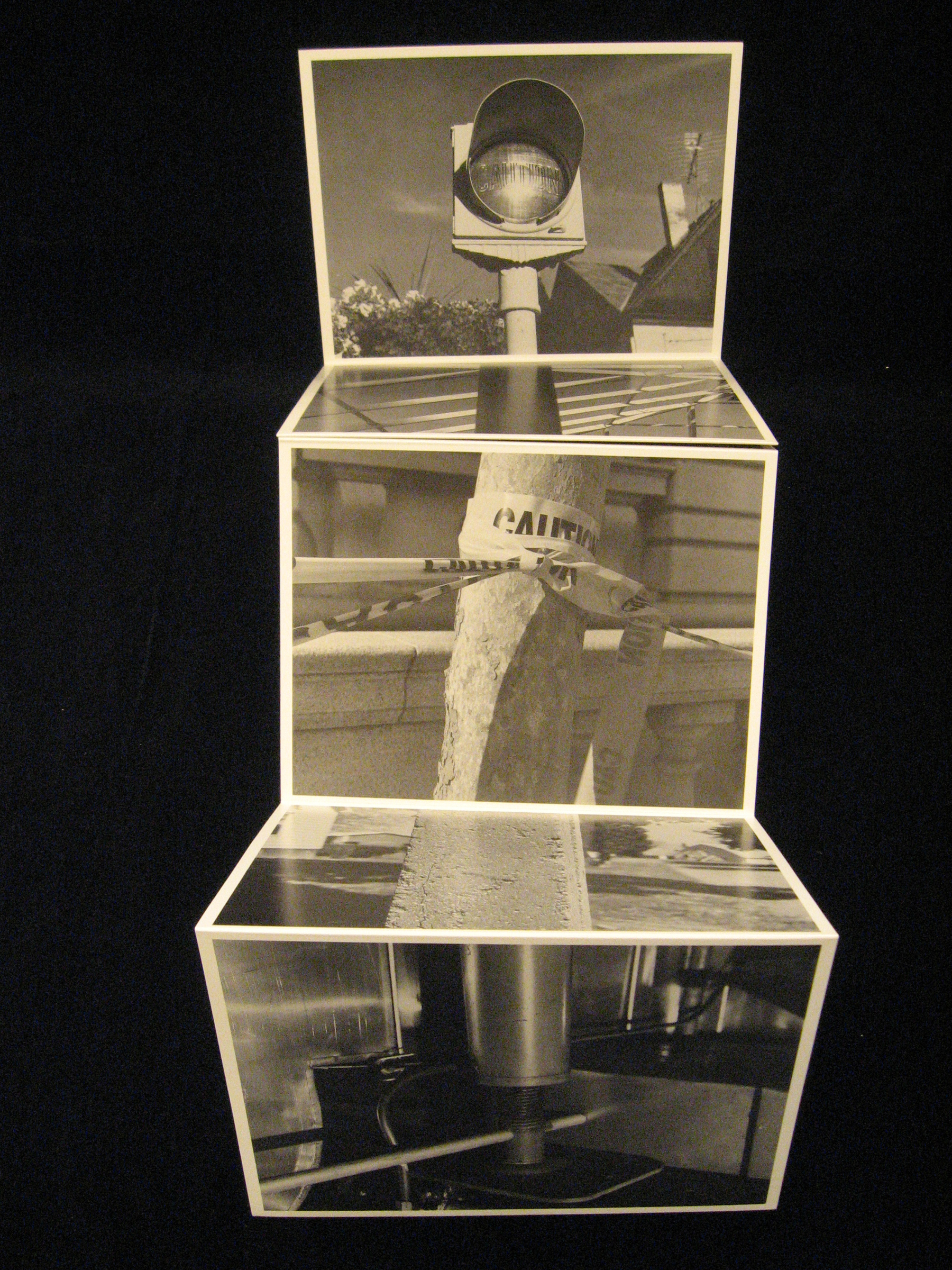 Open accordion fold book with black-and-white photos.