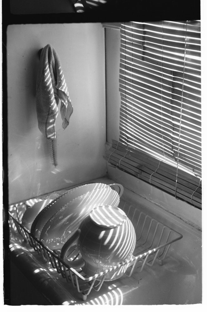 Dishes on kitchen sink in contrasting light and shadow. Image copyright Mark Strizic