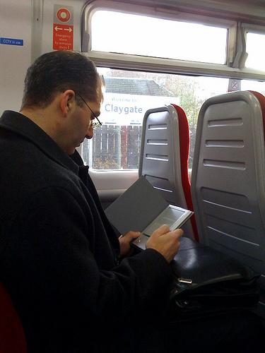 person using e-reader on train