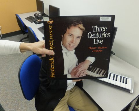 From the Sleeveface Friday gallery on the UNC Music Library's Facebook page, Sleeveface photo of student using midi keyboard in music library, incorporating vinyl sleeve of The Centuries Live by Frederick Moyer