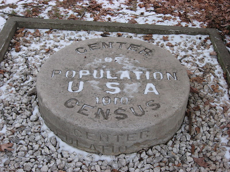 """A snow-covered, cricular stone marker reading """"Center of Population USA 1910 Census"""""""