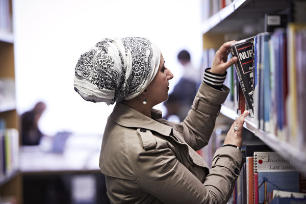 person looking at bookshelf