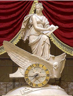 Ceramic sculpture depicting Clio the Muse of history holding an open book, half kneeling on a clock in the form of a winged chariot