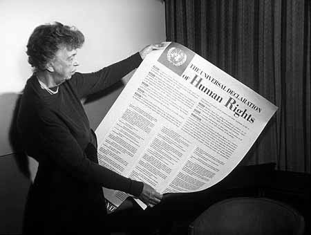 a black and white image of eleanor roosevelt holding a large document