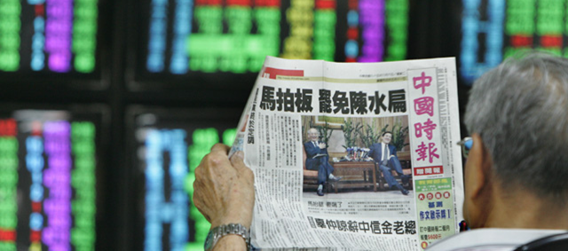 A photo of a man reading the Chinese Times newspaper.
