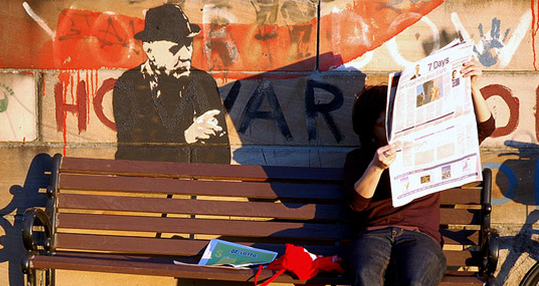 A photo of a man reading a newspaper.