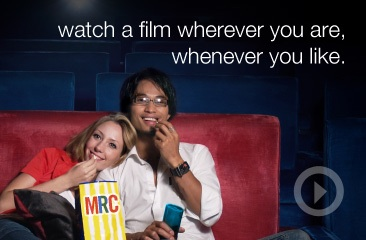 Two people watching a film with popcorn