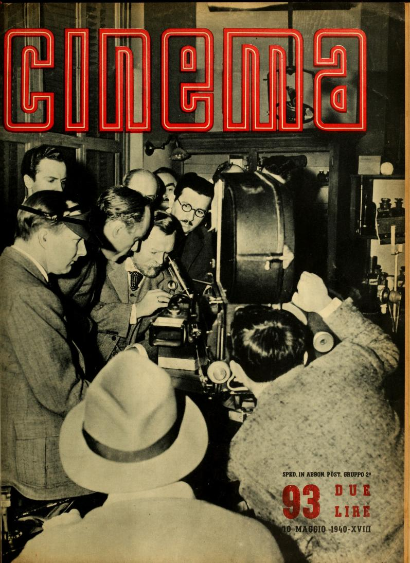 A group of people crowded around an old-fashioned movie camera