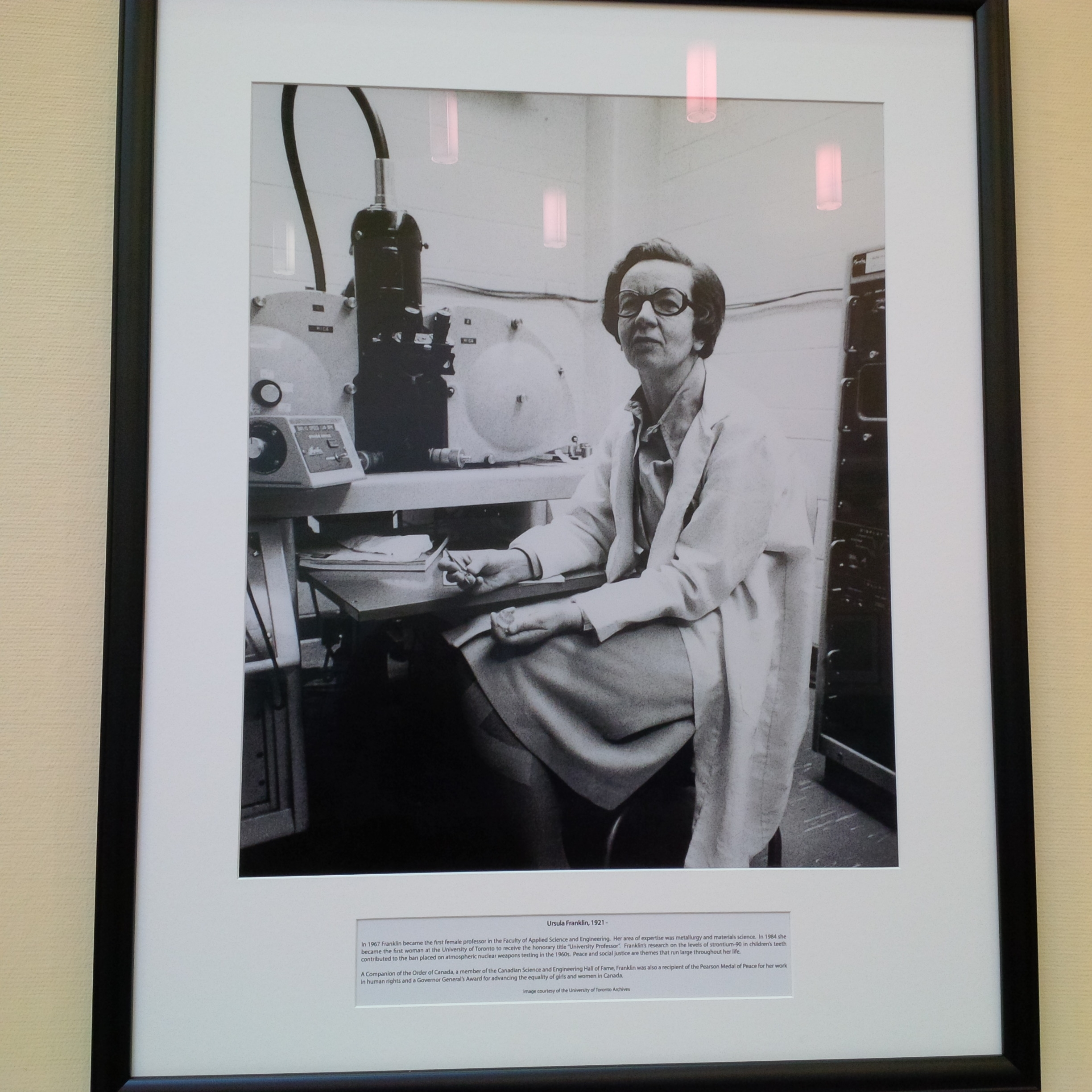 Framed black and white photo of lady scientis in lab coat - she is in front of a large lab machine