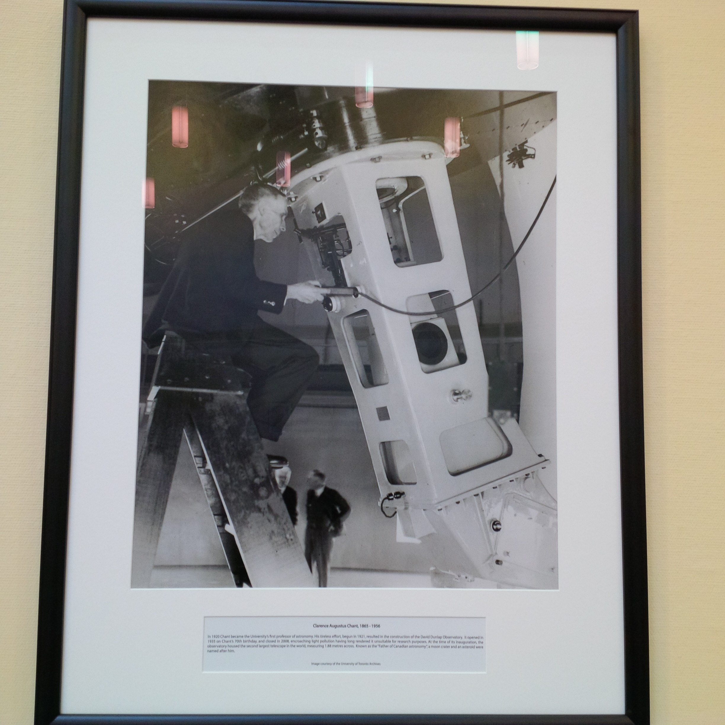 Black and white framed picture of man at telescope, sitting on ladder - two men are in the background
