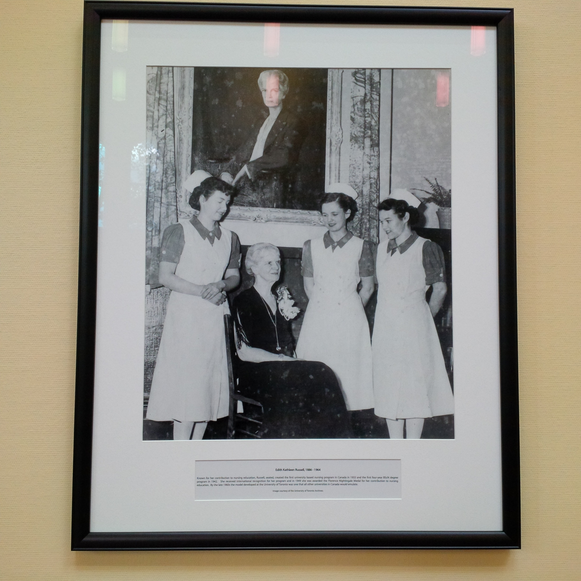 Framed photo of three nurses suround patient. Centred behind them is a large portrait
