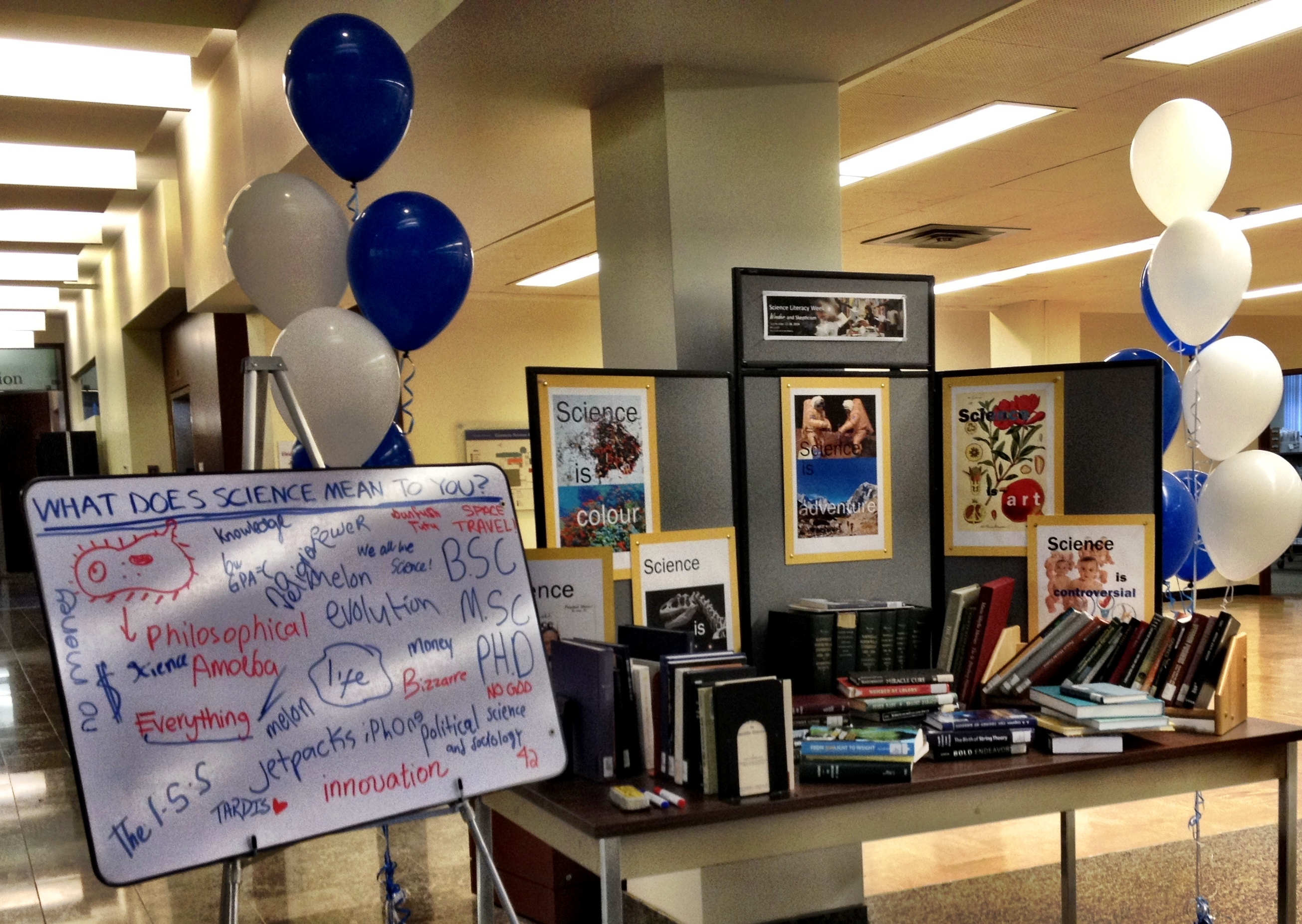 "Science books piled decoratively in front of science display board on a display table. Balloons surround the board and table. To the left, a white board states, ""What does science mean to you?"" Responses are written and drawn on the board, below the question."