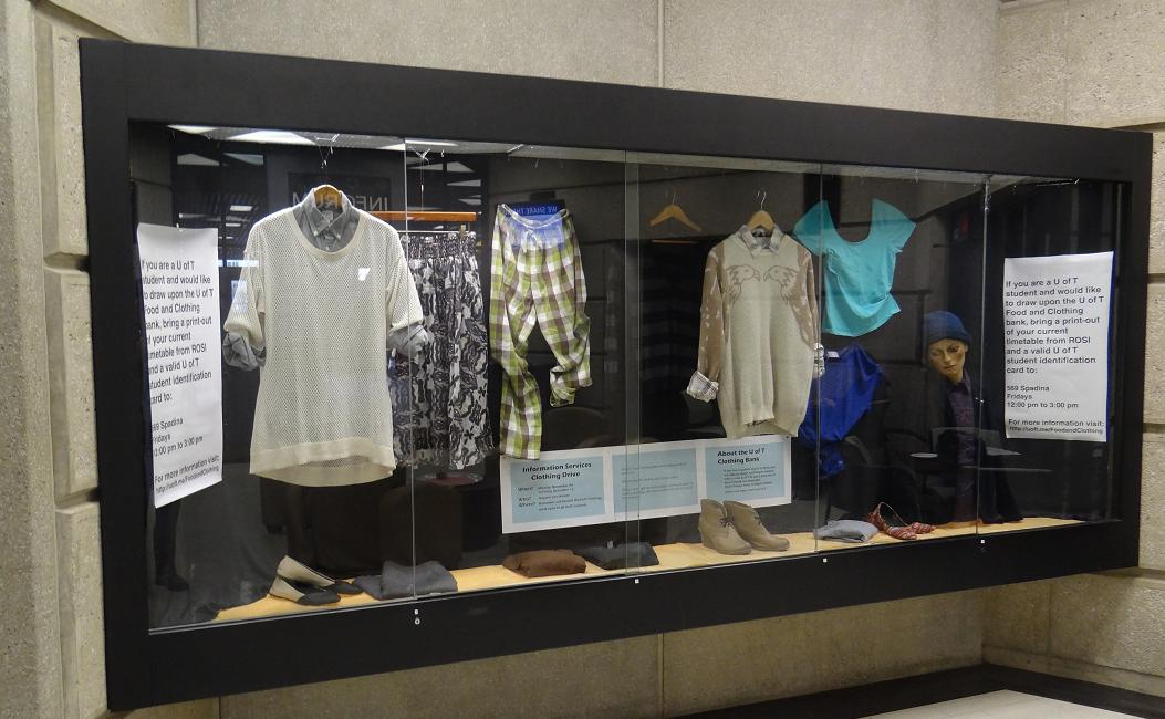 Glass display case of hung clothes and articles, like shoes, below. Signage to the light, lower middle, and right about accessing the U of T Clothing and Food Bank