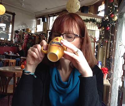 Picture of Maureen Morin, Sipping her coffee in a coffee shop decorated with Christmas apparel