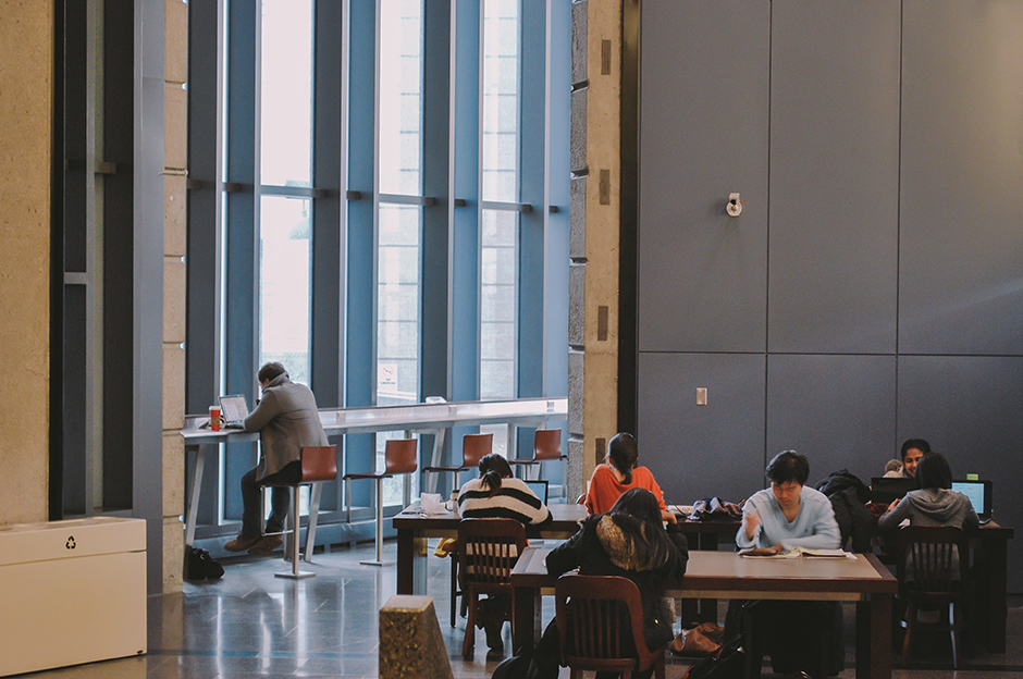 Picture of Robarts Library Study area - a bank of seating and workspace to the left (with large floor-to-ceiling windows); three work tables in front with groups of students